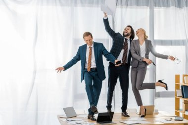 joyful insurance workers dancing on table and throwing papers at meeting in office