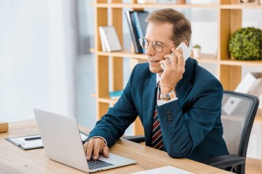 Adult smiling businessman in glasses talking on smartphone and using laptop in office stock vector