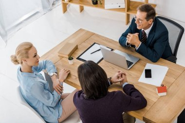 adult insurance agent in glasses talking to young couple in office