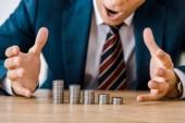 Fotografie zblízka překvapený podnikatel při pohledu na stříbrných mincí na dřevěný stůl