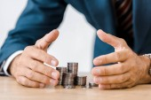 businessman grabbing silver coins at wooden table