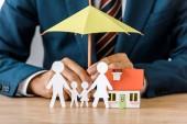 Fotografie Mužské ruce s papírem řez rodina, model domu a deštník na dřevěný stůl, životní pojištění