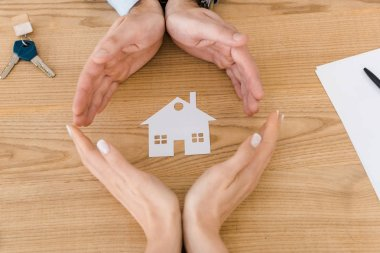 Couple making circle with hands with white paper house inside on wooden table, house insurance