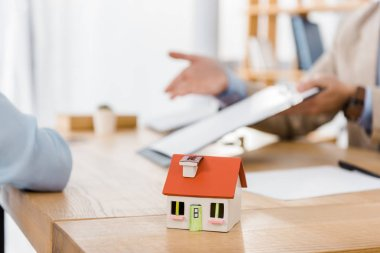 house model on wooden table with blurred people at background