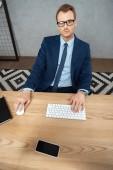 Fotografie erhöhte Ansicht der Geschäftsmann in Brillen, Blick in die Kamera und arbeiten am Tisch mit Computer-Tastatur, Maus und Smartphone mit leeren Bildschirm im Büro
