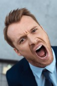 angry young businessman yelling and looking at camera in office