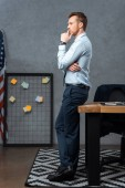 Photo side view of pensive young businessman standing in modern office