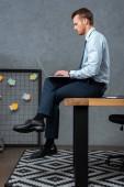 Jistý podnikatel sedí na stole a pracovat na notebooku v moderní kanceláři