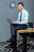 vážný podnikatel sedí na stole a pracovat na notebooku v moderní kanceláři
