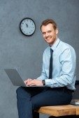 Photo happy young businessman sitting on table and working on laptop in modern office