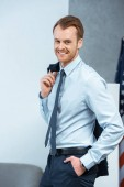 joyful young businessman with jacket over shoulder looking at camera in office