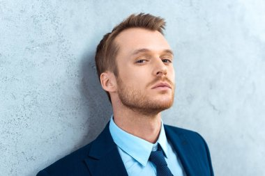 portrait of handsome businessman looking at camera near wall in office