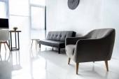 interiér moderního obývacího pokoje s počítačový monitor na stůl, křeslo a gauč