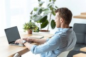 Photo selective focus of young businessman working on laptop with blank screen at table in office