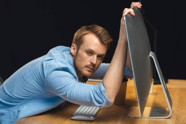 overworked young businessman holding computer monitor and looking at camera during night time in office