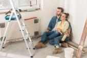 Fotografie vysoký úhel pohled zamyšlený mladý pár spolu sedí na podlaze a koukal na nový domov
