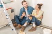 vysoký úhel pohledu usměvavý mladý pár drží papírových kelímků a sedí na podlaze v novém bytě
