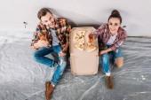 Fotografie pohled z šťastný mladý pár s pivo a pizza sedí na podlaze a usmívá se na kameru v novém bytě