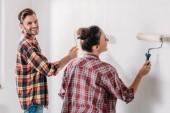 šťastný mladý pár v kostkované košile Malování zdi v novém bytě