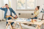 Photo tired young couple sitting near table with tools during house repairment