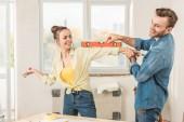 Fotografie glückliches junges Paar, das während der Reparatur Spaß mit Werkzeugen hat