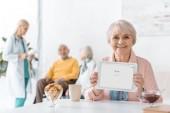 Starší žena držící digitální tablet s aplikací google v pečovatelském domě s lidmi v pozadí