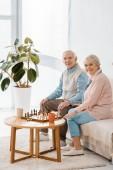 senior couple sitting on sofa and playing chess