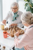 Fotografie senior women playing chess and drinking coffee in nursing home