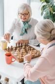Fotografie starší ženy hrát šachy a pití kávy v pečovatelském domě