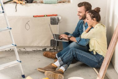 side view of happy young couple using laptop while sitting on floor in new house