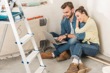 high angle view of young couple using laptop while sitting on floor in new house