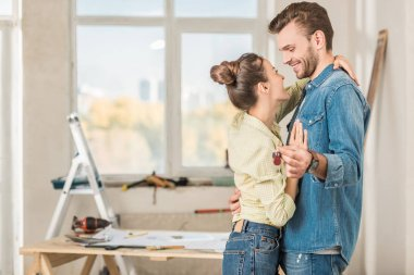 side view of happy young couple hugging during renovation at home