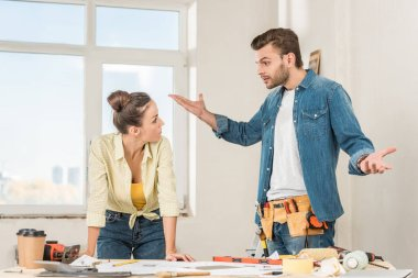 emotional young man gesturing and quarreling with girlfriend while discussing home repair