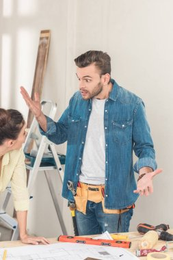 emotional young man gesturing and quarreling with girlfriend during house repair