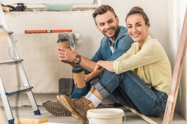 happy young couple holding paper cups and smiling at camera during house repair