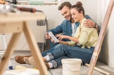 happy young couple using digital tablet during renovation in new house