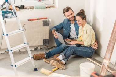 happy young couple using laptop during renovation in new house