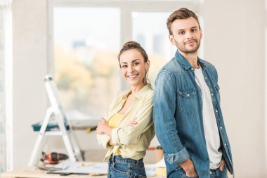 happy young couple standing back to back and smiling at camera in new house