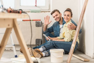 happy young couple using smartphone and smiling at camera while sitting on floor in new house