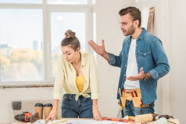 emotional young man with toolbelt gesturing and quarreling with girlfriend during house repair