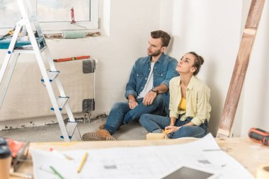 thoughtful young couple sitting in floor and looking away during house repair