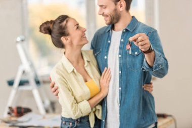happy young couple smiling each other and holding key from new house