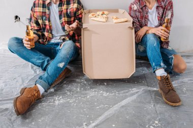 cropped shot of young couple holding beer bottles and sitting with pizza box in new apartment