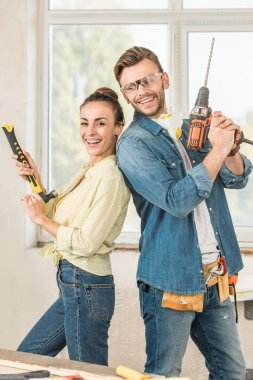 happy young couple holding hammer and electric drill during house repair