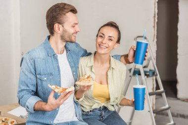 smiling young couple holding paper cups with drinking straws and pizza slices during repairment