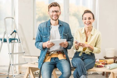 happy young couple using digital devices and smiling at camera during renovation