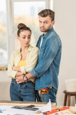 upset young man hugging disappointed girlfriend and looking at camera during house repair