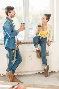 happy young couple holding paper cups with coffee to go and smiling each other in new home