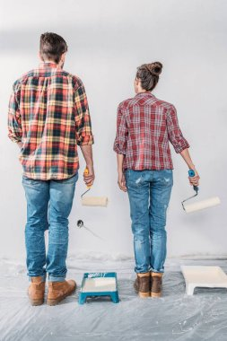 back view of young couple holding paint rollers and looking at wall in new house