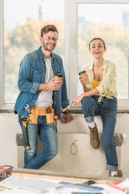 happy young couple holding coffee to go and smiling at camera during house repair